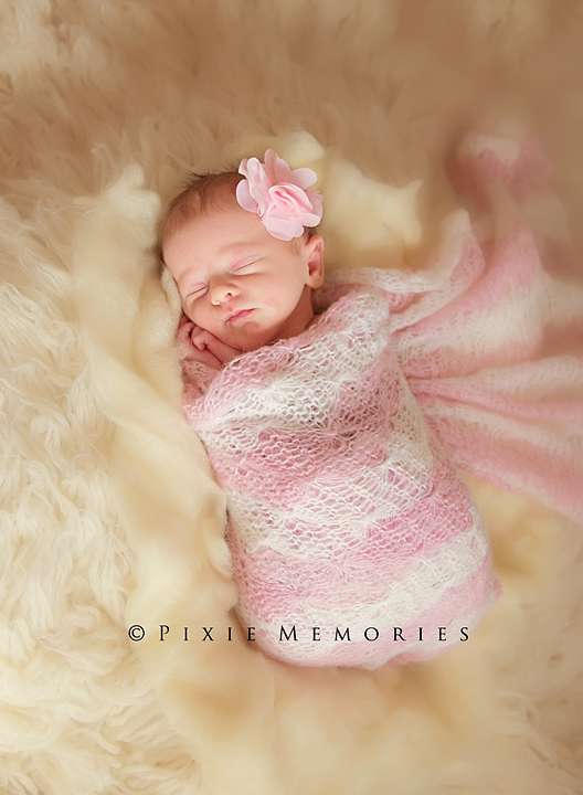 sleeping newborn in pink wrap